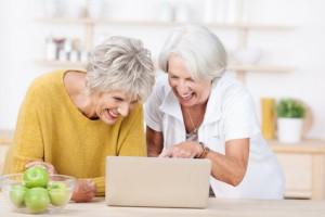 seniorinnen schauen auf laptop